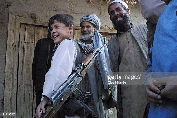 An Afghan boy carrying an assult rifle laughs with a group of men October 4 2001 in the front village of Jabul os Sarache 30 miles north of Kabul...