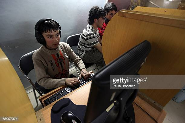 An Afghan boy checks his email at an internet cafe in Kabul City centre mall on February 12 2009 in Kabul Afghanistan The additional 17000 troops the...