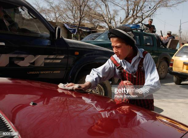 An Afghan boy cleans a car to help make money for his family after attending class at the Asciana school February 28 2008 in Kabul Afghanistan...
