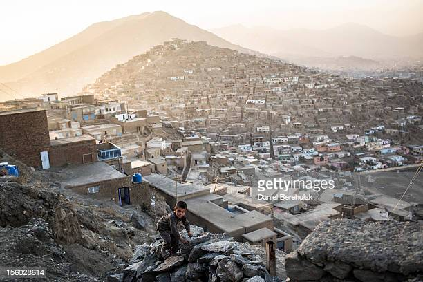 An Afghan boy climbs a rock fence on November 11 2012 in Kabul Afghanistan