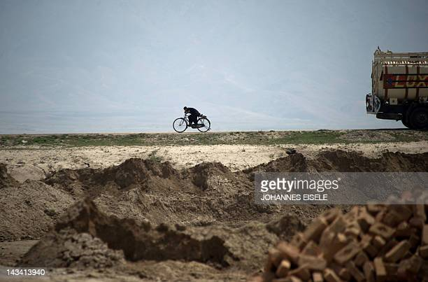 An Afghan boy cycles on the outskirts of the city of Kabul on April 26 2012 Poverty and an ongoing insurgency by the ousted Taliban still pose a...