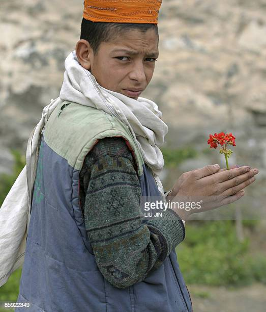 An Afghan boy holding a flower walks along a road in Naray, in Afghanistan's eastern Kunar province on April 13, 2009. US President Barack Obama,...