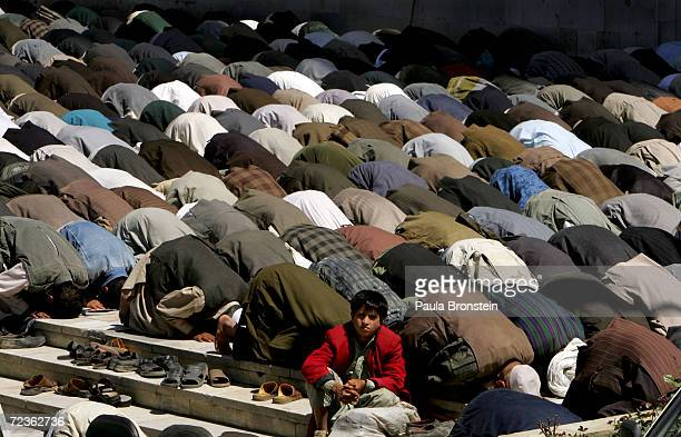 An Afghan boy is surrounded by men in prayer during Friday prayers at the Blue Mosque May 13 2005 in Kabul Afghanistan AntiAmerican protests...