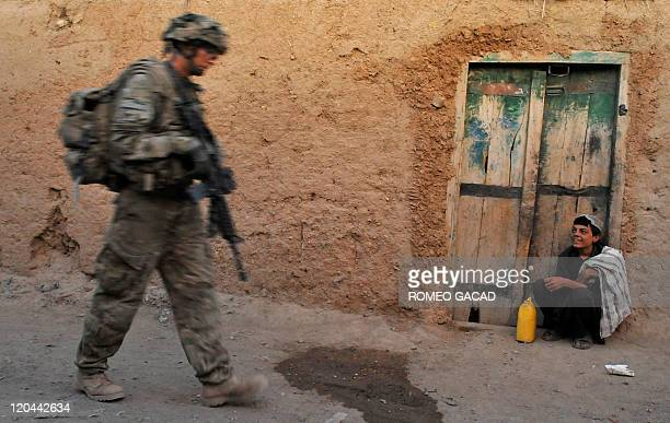 An Afghan boy looks at a US soldier from the 2nd Platoon Charlie Company 287 3BCT under Afghanistan's International Security Assistance Force during...