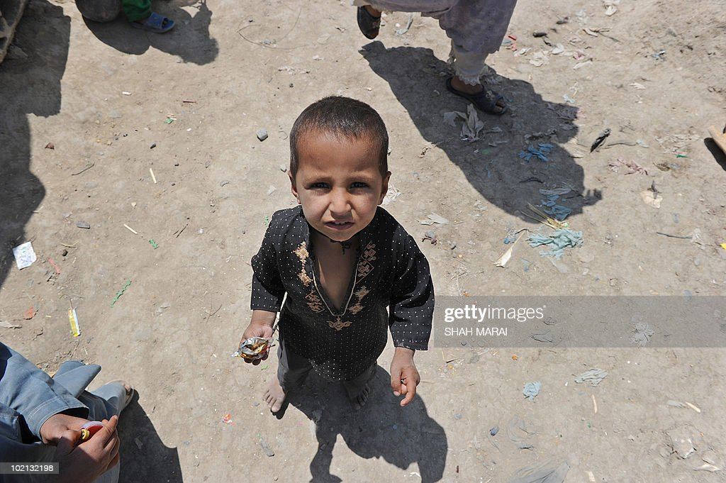An Afghan boy looks up as he stands next to his tent in Kabul on June 16, 2010. Afghanistan is one of the world's poorest countries where unemployment is at 40 percent and half the population is under the poverty line. AFP PHOTO/SHAH Marai