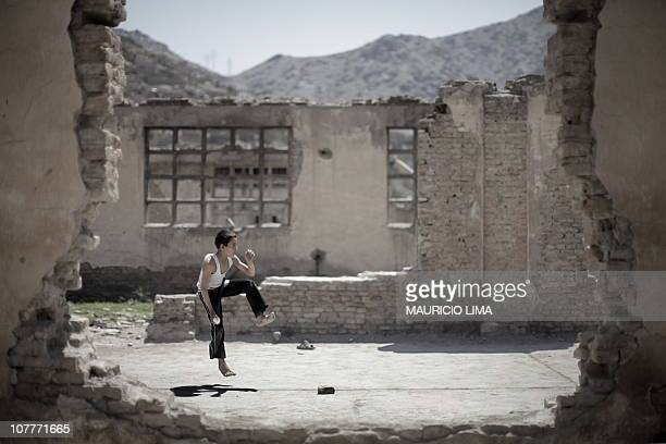 An Afghan boy prepares to bowl a ball while playing cricket inside the ruins of a compound which use to be home to a timber manufacturing factory in...