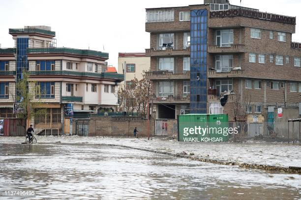 An Afghan boy rides his bicycle through flood waters along a roadside after heavy rains in Kabul on April 16 2019 Torrential rainstorms have lashed...