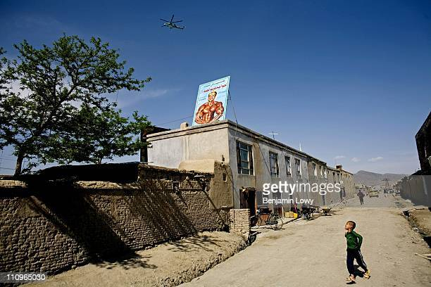 An Afghan boy runs down a Kabul side street past a small bodybuilding gym as an Afghan Army helicopter flies by on April 17,2007 in Kabul...