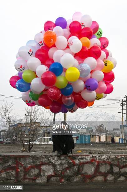 An Afghan boy selling balloons for Valentine's Day waits for customers on a roadside in Kabul on February 14 2019