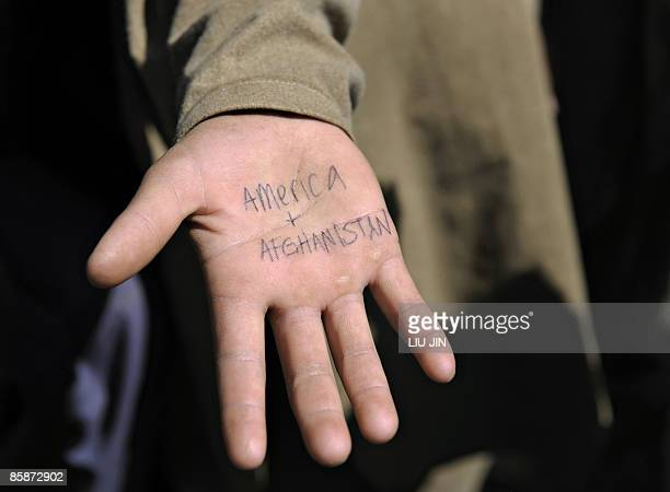 "An Afghan boy shows the characters reading ""America and Afghanistan"" on his hand written by a US soldier from 1st Infantry Division in Naray town, in..."