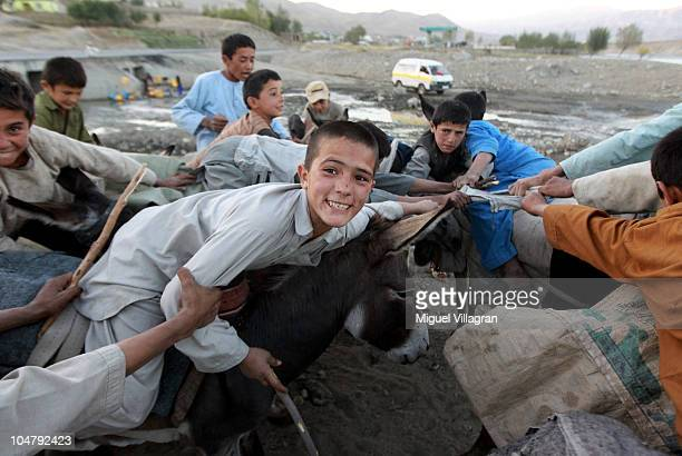 An Afghan boy smiles while he and his friends pretend to play Buzkashi on their donkeys as German soldiers patrol on October 5 2010 in Feyzabad...