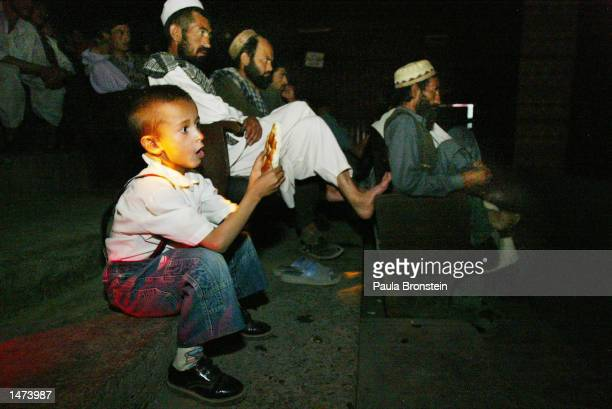 An Afghan boy watch a movie along side his father at he Park Cinema October14,2002 in Kabul, Afghanistan. Tickets cost around 10 cents . Only men are...