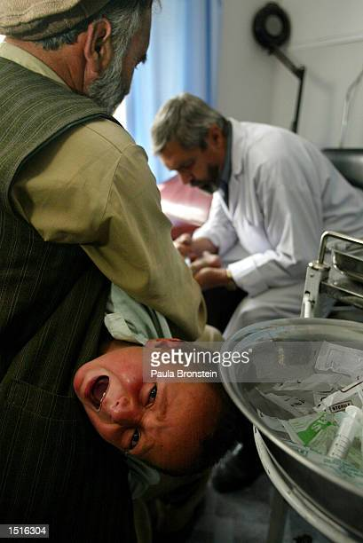An Afghan boy with Leishmaniasis cries while he gets an injection of Pentosam during his treatment at the Health Net Clinic October 23 2002 in Kabul...