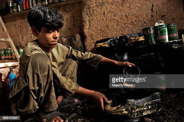 An Afghan boy works at an automobile workshop in the northwestern city of Herat Afghanistan May 6 2009 Young boys who join as '˜shagrid' at the...