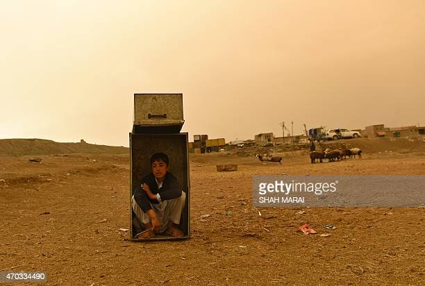 An Afghan boy youth sits in a box as he takes shelter from the rain in Kabul on April 19 2015 AFP PHOTO / SHAH Marai