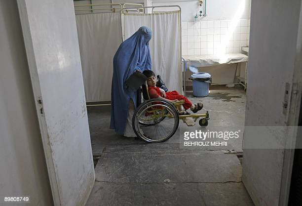 An Afghan burqaclad woman and her mentally disabled daughter wait for the doctor at the Emergency Ward of Herat Hospital in the western city of Herat...