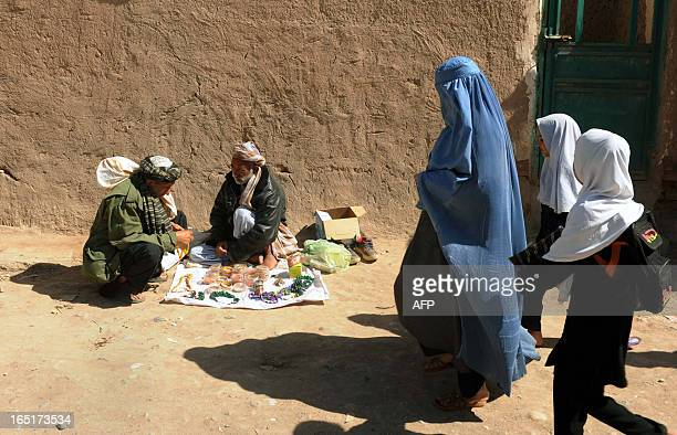 An Afghan burqaclad woman and two school girls walk in the old part of Herat city on April 1 2013 Some nine million Afghans or 36 percent of the...