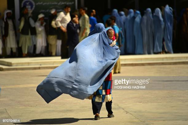 TOPSHOT An Afghan burqaclad woman walks a she hold a child before receiving aid by a charity during the holy month of Ramdan in Herat province on...
