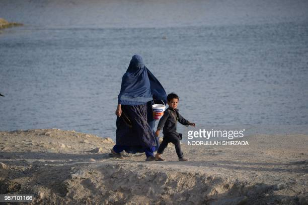 An Afghan burqaclad woman walks with her son on the outskirts of Kabul on June 29 2018