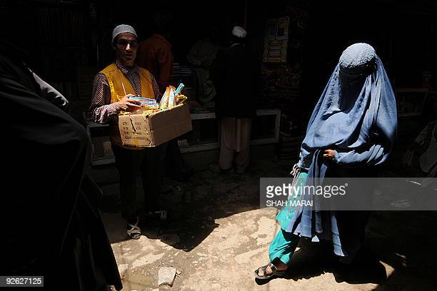 An Afghan caries his wares as a burqaclad woman walks in the old city of Kabul on July 6 2009 Afghans go to the polls on August 20 to elect a...