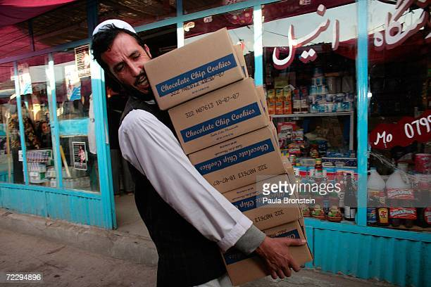 An Afghan carries Chocolate chip cookies to his shop at the Bush Bazaar October 29 2006 in Kabul Afghanistan The small black market named after US...