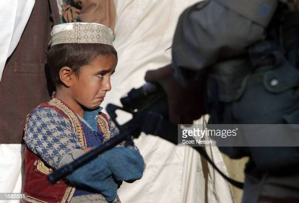 An Afghan child begins to cry as he and his father are guarded by soldiers from the US Army 82nd Airborne as they conduct a sweep of homes in the...