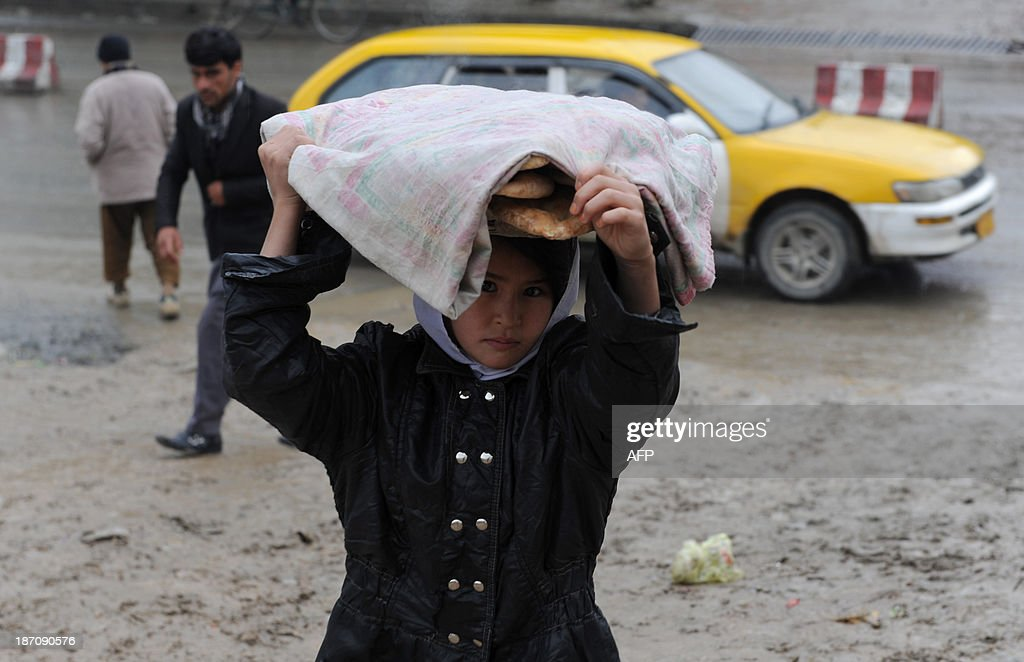 An Afghan child carries bread on her head through rain in Kabul on November 06, 2013. Despite massive injections of foreign aid since the fall of the Taliban in 2001, Afghanistan remains desperately poor as it attempts to recover from decades of conflict. AFP PHOTO / Farshad USYAN
