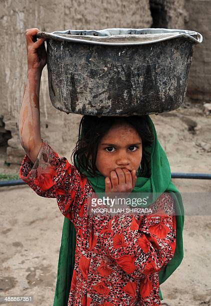 An Afghan child carries water through the temporary settelment where she lives on the outskirts of Jalalabad on May 8 2014 Afghanistan's economy is...