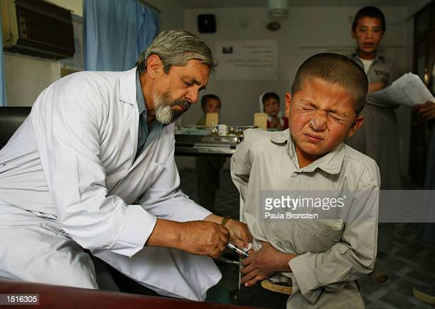 An Afghan child gets treated for Leishmaniasis by Dr. Fakhria with an injection of Pentostam at the Health Net Clinic October 23, 2002 in Kabul,...