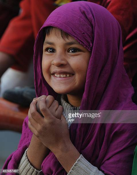 An Afghan child looks on as performers from The Mobile Mini Circus for Children take part in a circus show in Kabul on November 29, 2013. The Mobile...