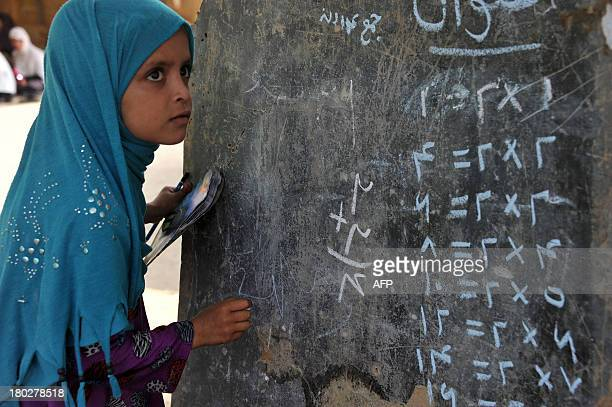 An Afghan child looks up at a blackboard in an open classroom on the outskirts of Jalalabad on September 11 2013 Afghanistan has had only rare...