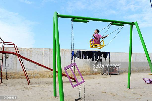 An Afghan child plays on a swing at the Balkh Orphanage in the outskirts of Mazar i Sharif on October 15 2012 Some 58 children mostly boys live here...