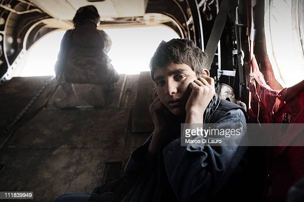 An Afghan child puts his hands over his ears to shield himself from the noise, the surroundings and probably the trauma as British soldiers carry on...