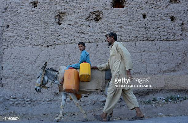 An Afghan child rides a donkey carrying containers past the ruins of a building destroyed during the AfghanSoviet war on outskirts of Jalalabad in...