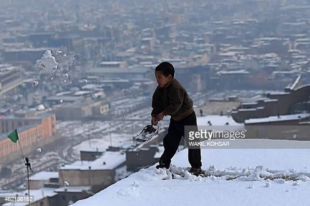 An Afghan child shovels snow from the roof of his house overlooking Kabul on January 25 2015 The Afghan capital witnessed its first snowfall of the...
