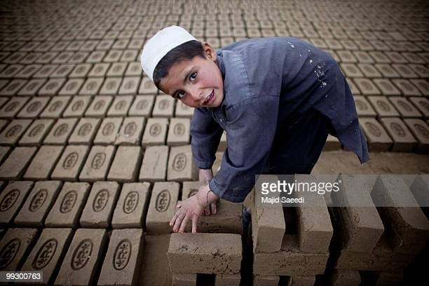 An Afghan child sorts bricks at the Sadat Ltd Brick factory where he works from 8am to 5 pm daily on May 14 2010 in Kabul Afghanistan Child labour is...