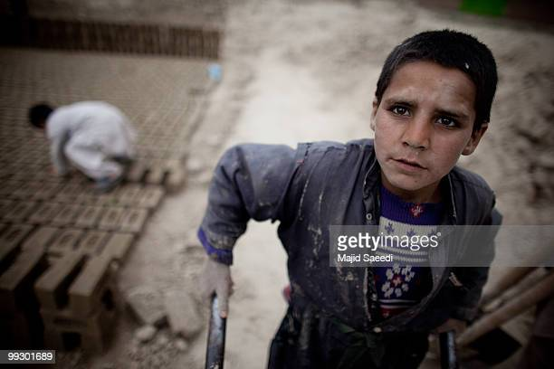 An Afghan child transports bricks at the Sadat Ltd. Brick factory, where he works from 8am to 5 pm daily, on May 14, 2010 in Kabul, Afghanistan....