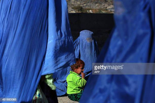 An Afghan child wearing a green fleece sits with her burqaclad mother asking for alms as women in blue burqas walk past in Kabul on November 25 2013...