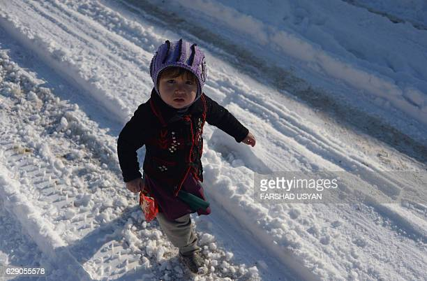 An Afghan child who was displaced by Kunduz fighting between Afghan forces and Taliban insurgents walks in the snow at a refugee camp in MazariSharif...