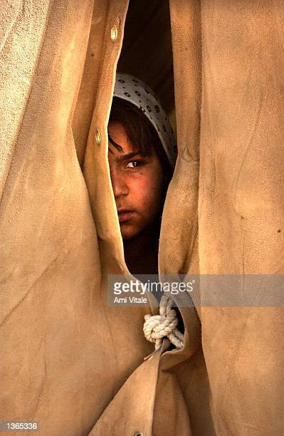 An Afghan child who was living in camps around Spin Boldak near the border of Pakistan in southern Afghanistan looks out of her new home after she...