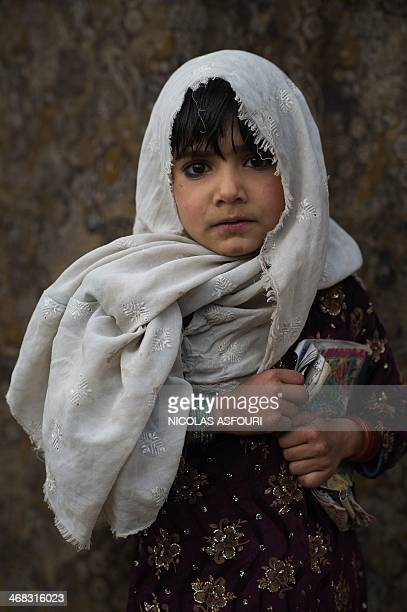 An Afghan child whose family fled their home country to Pakistan stands outside her home in a slum on the outskirts of Islamabad on February 10 2014...