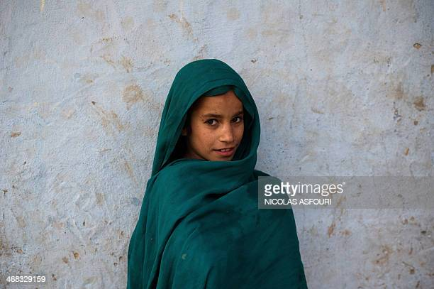 An Afghan child whose family fled their home country to Pakistan stands outside her makeshift shelter in a slum on the outskirts of Islamabad on...