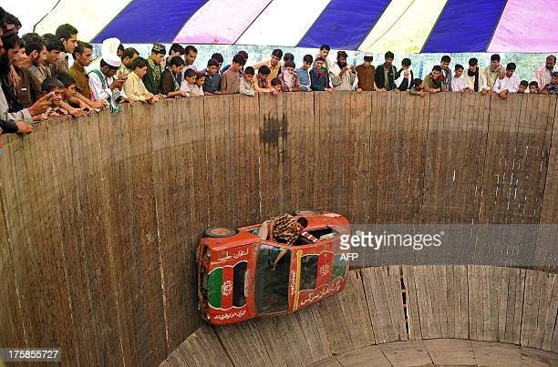 An Afghan circus performer drives a car on the ' Wall of Death' at a fair on the second day of Eid alFitr in Jalalabad on August 9 2013 Muslims...