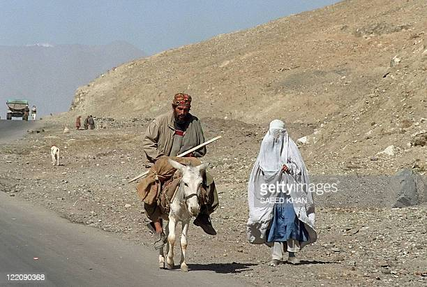 An Afghan civilian flees from frontline areas on his donkey while his wife walks beside him 01 November 1996 Hundreds of villagers moved from...