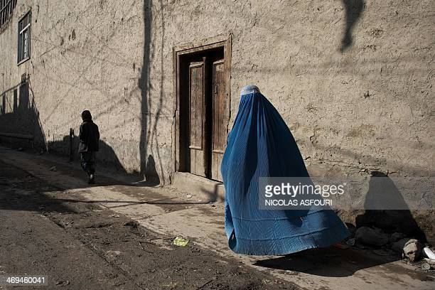 An Afghan cladburqa woman walks down a street in Kabul on February 15 2014 Some nine million Afghans or 36 percent of the population are living in...