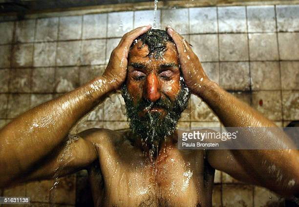 An Afghan coal miner showers in the bath house cleaning off the coal after his shift is done on the grounds of the Karkar mine October 31 2004 Karkar...