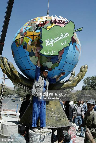 An Afghan construction crew aligns a globe into a pair of open hands on a statue being completed in honor of Commander Ahmad Shah Massoud's third...