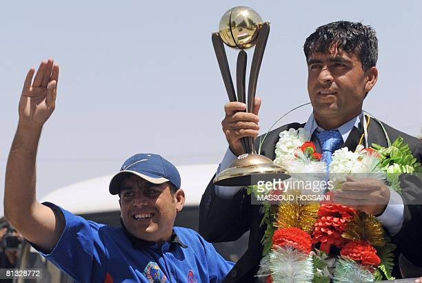 An Afghan cricket player from the national cricket team holds a trophy upon their return to the country following their qualification for the ICC...