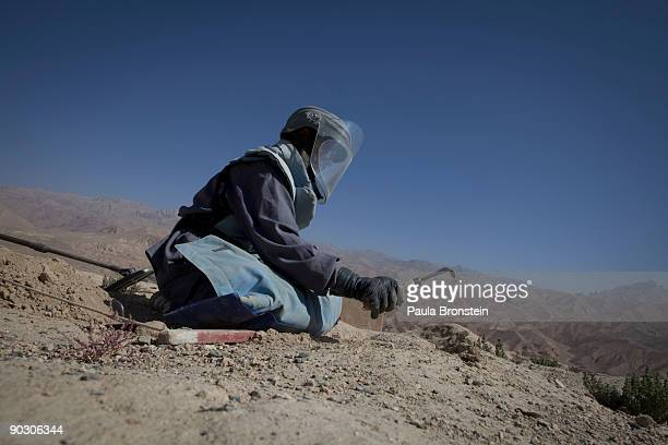 An Afghan deminer digs searching for mines and other munitions on top the archaelogical site of ShahriGholghola September 2 2009 in Bamiyan...
