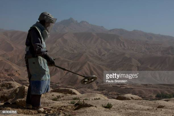 An Afghan deminer uses a metal detector to search for ordinance on top the archaelogical site of ShahriGholghola on September 2 2009 in Bamiyan...